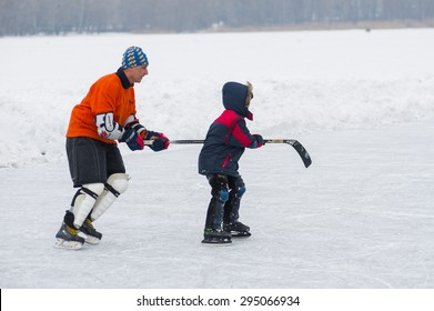 Dnepropetrovsk, Ukraine - February 08, 2014: Active father teaches son skating helping with hockey stick on a frozen river Dnepr