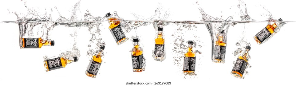 Dnepropetrovsk, Ukraine - January 06, 2015: Bottles of whiskey Jack Daniels falling into water. studio shooting