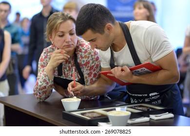DNEPROPETROVSK, UKRAINE - MAY 30, 2013: Judges estimate the foam during 5th Ukrainian Latte Art Championship in Dnepropetrovsk, Ukraine on May 30, 2013