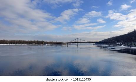 Dnieper River in Kiev, Pedestrian bridge. Reflection of the sky. Winter