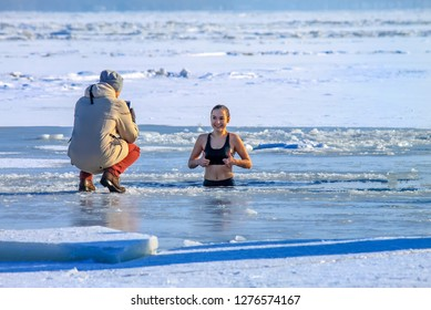 Dnipro city, Ukraine 19 01 2017. Winter sport. Beautiful happy girl swims  in the winter river covered with ice during the Orthodox holiday of Epiphany. Hardening. Dnepropetrovsk