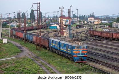 Dnipro, Ukraine - 05/28/2020: An electric locomotive VL8M-758 pulls freight cars at the Nizhnedneprovsk-Uzel marshalling railway station