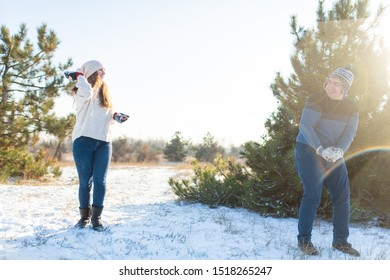 Dnipro / Ukraine - 12.02.2018: Loving couple play snowballs in winter in the forest. Throw each other snow. Laugh and have a good time.