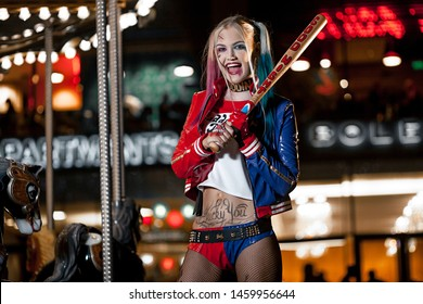 Dnipro, Ukraine - August 17, 2016: Portrait of smiling cosplayer girl in costume Harley Quinn on background lights of night city. Cosplay