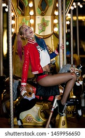 Dnipro, Ukraine - August 17, 2016: Smiling cosplayer girl in costume Harley Quinn on background lights of carousel ride. Cosplay