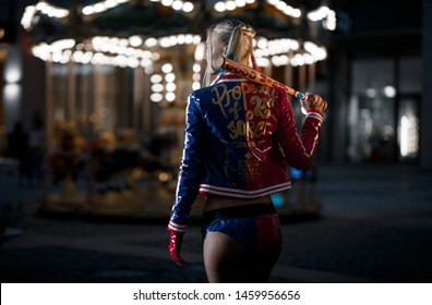 Dnipro, Ukraine - August 17, 2016: Cosplayer girl in costume Harley Quinn on background lights of night city. Cosplay.