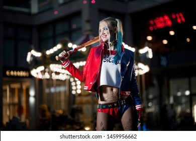 Dnipro, Ukraine - August 17, 2016: Smiling cosplayer girl in costume Harley Quinn on background lights of night city. Cosplay