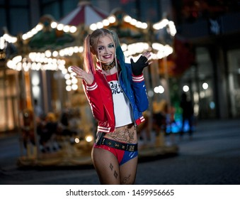 Dnipro, Ukraine - August 17, 2016: Smiling girl in costume Harley Quinn on background of night city lights. Cosplay