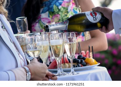 Dnipro, Ukraine - august 25, 2017: waiter pours Italian sparkling wine Martini Asti into glasses on the buffet table with fruits