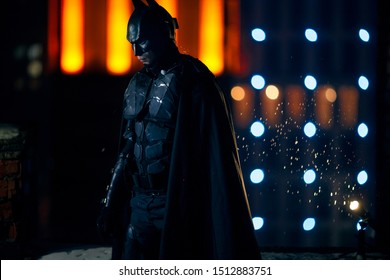 Dnipro, Ukraine - December 5, 2018: Batman superhero character of DC Comics dressed in mask, helmet, armor and black cloak stands against the background of night city lights and buildings. Cosplay.
