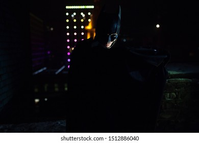 Dnipro, Ukraine - December 5, 2018: Batman superhero character of DC Comics dressed in mask, helmet, armor and cloak stands against the background of night city lights and buildings. Cosplay. Closeup.