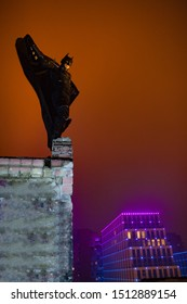 Dnipro, Ukraine - December 5, 2018: Batman superhero character of DC Comics dressed in mask, helmet, armor and cloak stands at the top of the building against the background of night city lights.