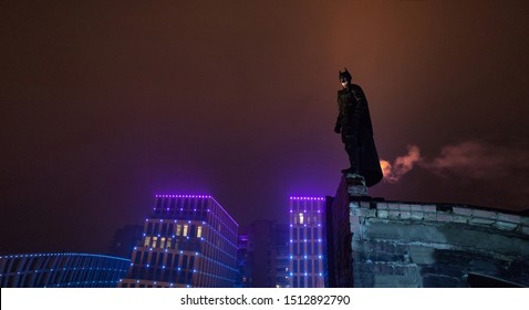 Dnipro, Ukraine - December 5, 2018: Batman superhero character of DC Comics  dressed in mask, helmet, armor and cloak stands at top of building against the background of night city lights and sky.
