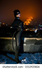 Dnipro, Ukraine - December 5, 2018: Catwoman superhero character of DC Comics stands against the background of night city lights and sky. Cosplay.
