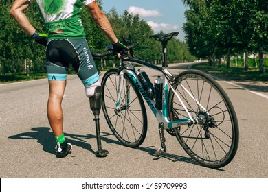 Dnipro, Ukraine - July 12, 2019: athlete with disabilities or amputee training in cycling. Professional sportsman with leg prosthesis resting before start outdoors. Disabled sport, healthy lifestyle.