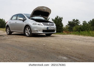 Dnipro, Ukraine - July 30, 2021: Toyota Auris 2012 silver color with open hood. Summer rain