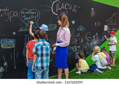 Dnipro, Ukraine - June 27, 2018: Marina Poroshenko with children draws scrawl chalk on a blackboard in inclusive gaming park of the city