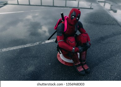DNIPRO, UKRAINE - MARCH 28, 2019: Deadpool cosplayer posing sitting with weapon behind his back.