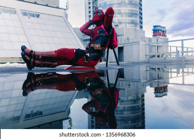 DNIPRO, UKRAINE - MARCH 28, 2019: Deadpool cosplayer posing sitting with weapon behind his back on background on his reflection in water.