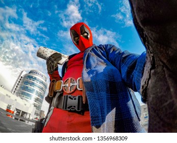 DNIPRO, UKRAINE - MARCH 28, 2019: Deadpool cosplayer posing against the background of the urban landscape and sky with clouds.