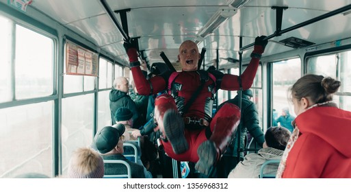 DNIPRO, UKRAINE - MARCH 28, 2019: Deadpool cosplayer has fun and rides the city tram with guns and katanas behind his back.