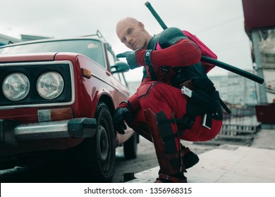 DNIPRO, UKRAINE - MARCH 28, 2019: Deadpool cosplayer posing with gun and katanas behind his back next to the retro car.