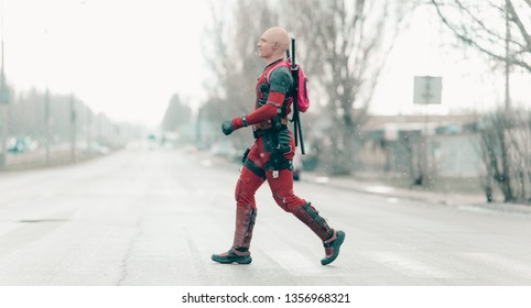 DNIPRO, UKRAINE - MARCH 28, 2019: Deadpool cosplayer crossing the city street with guns and katanas behind his back during rain.