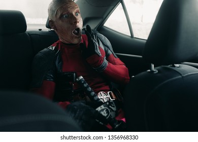 DNIPRO, UKRAINE - MARCH 28, 2019: Deadpool cosplayer posing in the car with weapon in his hands.