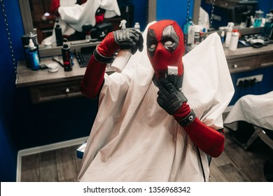 DNIPRO, UKRAINE - MARCH 28, 2019: Deadpool cosplayer is posing and sitting on armchair in barbershop.