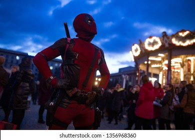 DNIPRO, UKRAINE - MARCH 28, 2019: Deadpool cosplayer posing with guns and katanas behind his back against the background of night city lights.