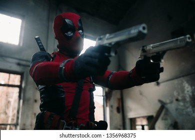 DNIPRO, UKRAINE - MARCH 28, 2019: Deadpool cosplayer posing indoors with two guns in his hands and katanas behind his back.