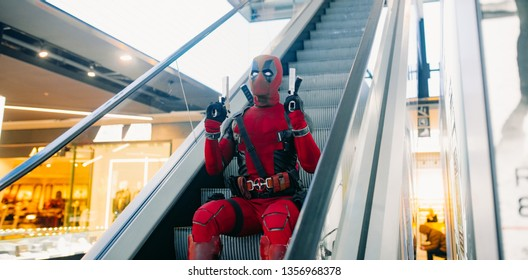 DNIPRO, UKRAINE - MARCH 28, 2019: Deadpool cosplayer posing with guns in his hands on background of escalator staircase.
