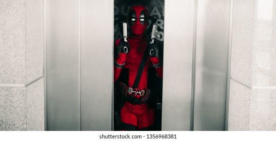 DNIPRO, UKRAINE - MARCH 28, 2019: Deadpool cosplayer posing with guns in his hands on background of lift door.