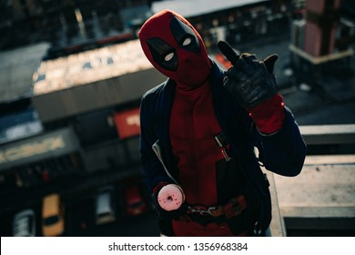 DNIPRO, UKRAINE - MARCH 28, 2019: Deadpool cosplayer posing with cake in his hand on background of city street.
