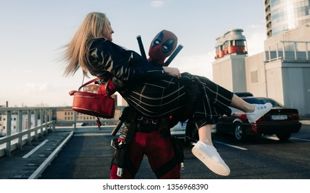 DNIPRO, UKRAINE - MARCH 28, 2019: Deadpool cosplayer has fun and carries girl on his hands with guns and katanas behind his back.