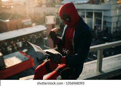 DNIPRO, UKRAINE - MARCH 28, 2019: Deadpool cosplayer posing with cake and newspaper in his hands on background of city street.
