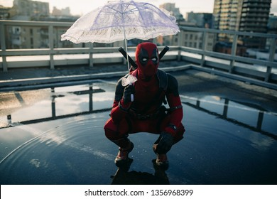 DNIPRO, UKRAINE - MARCH 28, 2019: Deadpool cosplayer posing with weapon and umbrella on background the urban landscape.