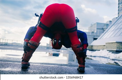 DNIPRO, UKRAINE - MARCH 28, 2019: Deadpool cosplayer is posing and bending down against the background of the urban landscape.