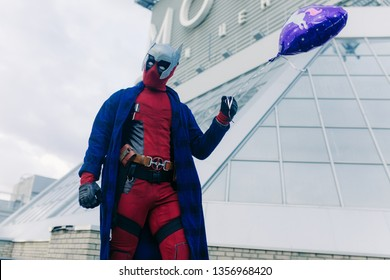 DNIPRO, UKRAINE - MARCH 28, 2019: Deadpool cosplayer posing with air balloon in his hand against the background of the urban landscape.