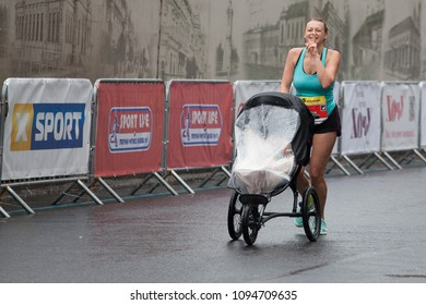 Dnipro, Ukraine -  May 20, 2018: Interpipe Dnipro Half Marathon. Young mother with finger on lips asking for silence runnig with a child in a stroller