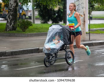 Dnipro, Ukraine -  May 20, 2018: Interpipe Dnipro Half Marathon. Young mother runnig with a child in a stroller