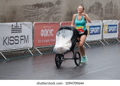 Dnipro, Ukraine -  May 20, 2018: Interpipe Dnipro Half Marathon. Young mother runnig with a child in a stroller and showing Like gesture