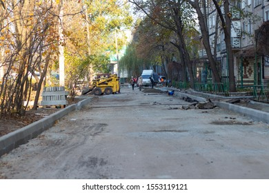 Dnipro, Ukraine - October 31, 2019: road repair, a tractor stands on a repaired road along a residential building in the cities of Dnieper Ukraine