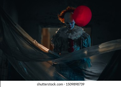 "Dnipro, Ukraine - September 8, 2019: Cosplayer in the image of a Pennywise the Dancing Clown from horror movie ""It"" stands in old abandoned building with red balloon in his hand."