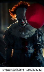 "Dnipro, Ukraine - September 8, 2019: Portrait of a cosplayer in the image of a Pennywise the Dancing Clown from horror movie ""It"" with red balloon in his hand with backlight."