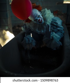 "Dnipro, Ukraine - September 8, 2019: Cosplayer in the image of a Pennywise the Dancing Clown from horror movie ""It"" stands in old abandoned building with red balloon in his hand ."