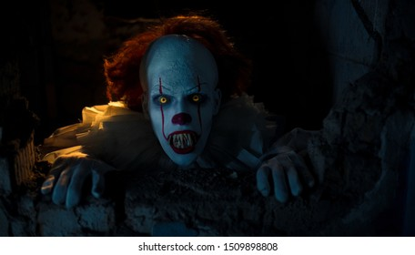 "Dnipro, Ukraine - September 8, 2019: Portrait of a cosplayer in the image of a Pennywise the Dancing Clown from horror movie ""It"" with fangs and scary grin. Backlight."