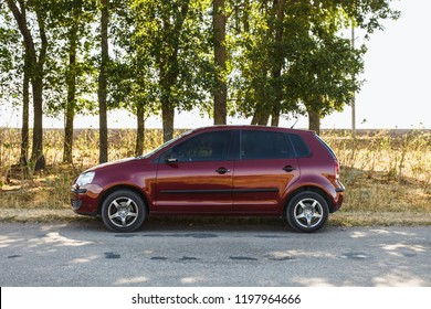 DNIPROPETROVSK REGION, UKRAINE - AUGUST 23, 2016: Volkswagen Polo burgundy color on the road near the line of trees, summer time in rural