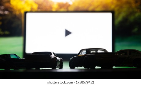 DNIPRO/UKRAINE - 06.18.2020: Drive-in theater or drive in cinema, open air movie. Cars on the background of a large movie screen, outdoors.