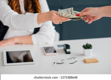 Do business online, get cash salary. Female extending dollar bills. Making money on internet. Income, payment, funds.